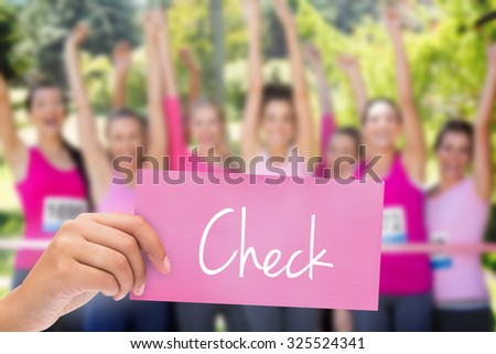 The word check and hand holding card against smiling women running for breast cancer awareness - stock photo