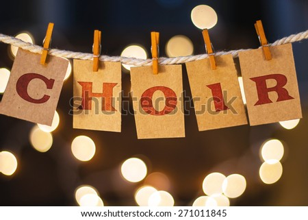 The word CHOIR printed on clothespin clipped cards in front of defocused glowing lights. - stock photo