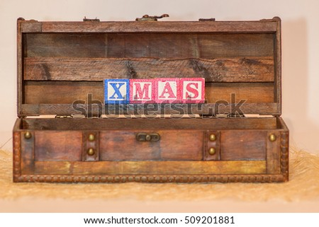 The word Christmas written with blue and red wooden letter blocks in a dark brown wood chest on white background