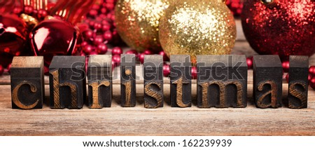 The word CHRISTMAS written with vintage wood printer blocks. Christmas message over old wood with traditional tree decorations behind. - stock photo
