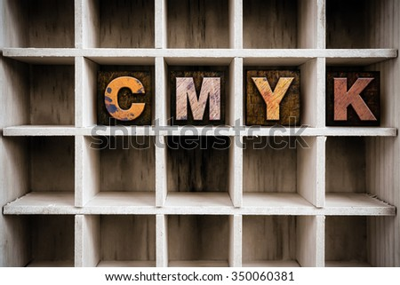 "The word ""CMYK"" written in vintage ink stained wooden letterpress type in a partitioned printer's drawer. - stock photo"