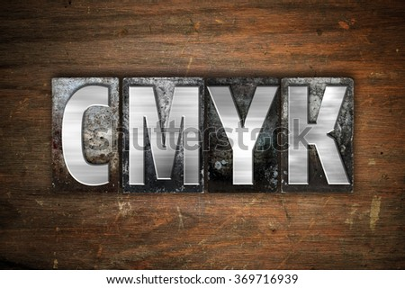 """The word """"CMYK"""" written in vintage metal letterpress type on an aged wooden background. - stock photo"""