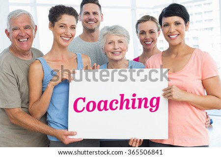 The word coaching and fit people holding blank board in yoga class against grey wall