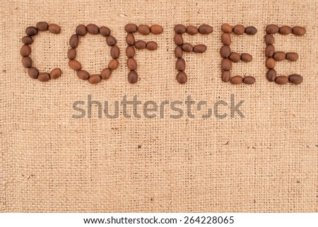 The word coffee made from coffee beans on burlap background
