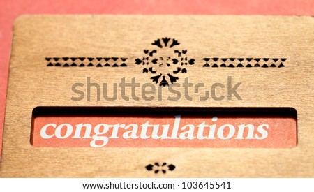 The word Congratulations is highlighted with a wooden decoration board - stock photo