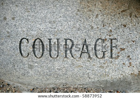 the word courage carved onto a granite cobble stone