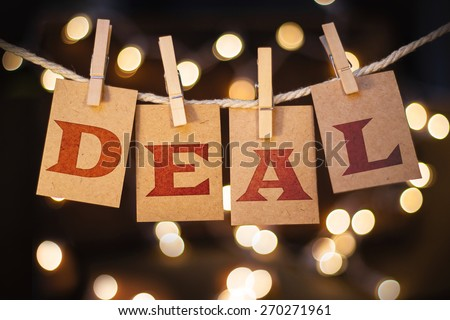 The word DEAL printed on clothespin clipped cards in front of defocused glowing lights. - stock photo