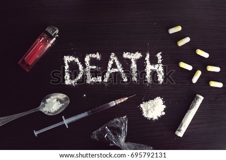 The word death written in cocaine on a black table surrounded by various hard drugs. The concept of addiction.