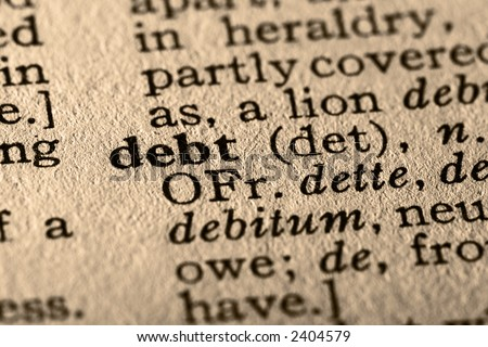 The word debt. Close-up of the word debt in a dictionary. - stock photo