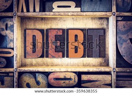"The word ""Debt"" written in vintage wooden letterpress type. - stock photo"