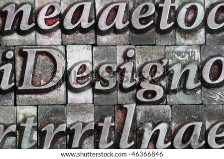 the word design in letterpress type surrounded with random letters. - stock photo