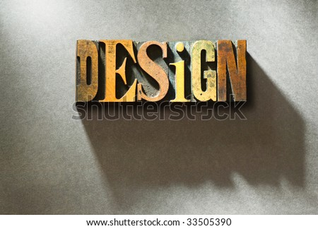 The word Design in random wooden letterpress characters on gray paper background. - stock photo