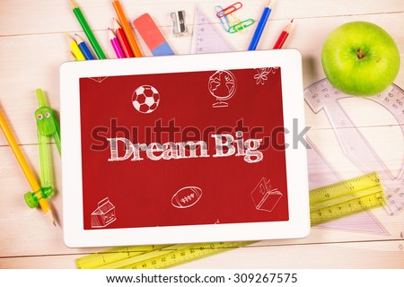 The word dream big and school doodles against students desk with tablet pc