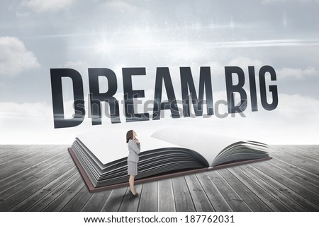 The word dream big and smiling thoughtful businesswoman against open book against sky - stock photo
