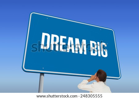 The word dream big and thinking businesswoman against bright blue sky - stock photo