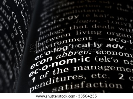 The word economic in a dictionary, white on black - stock photo