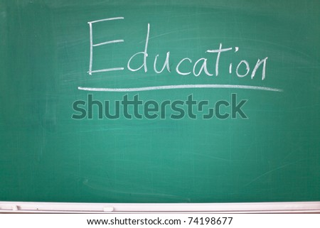 """The word """"Education"""" spelled with white chalk on green blackboard. - stock photo"""