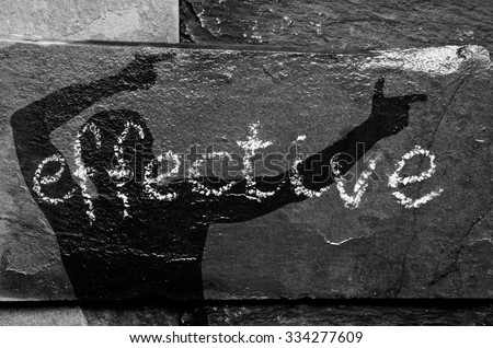 The word EFFECTIVE written with chalk on black stone with man shadow on it.