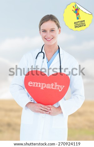 The word empathy and doctor holding red heart card against bright brown landscape - stock photo