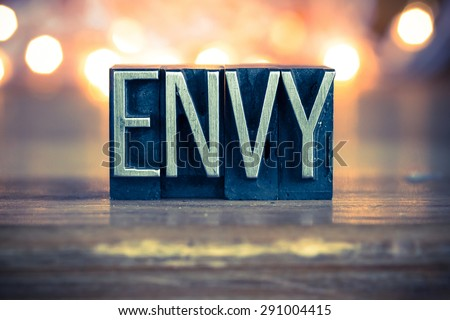 The word ENVY written in vintage metal letterpress type on a soft backlit background. - stock photo