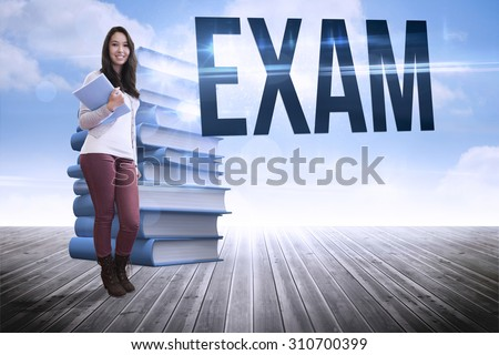 The word exam and smiling student holding textbook against stack of books against sky - stock photo