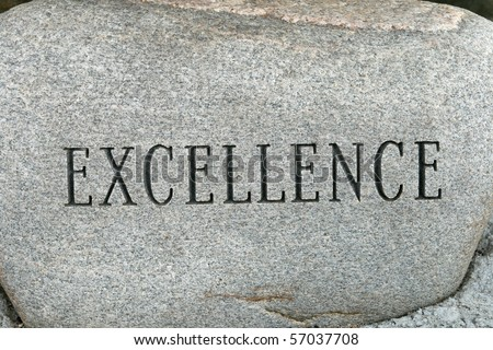the word excellence carved onto a granite cobble stone