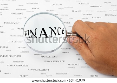 The word FINANCE is magnified. - stock photo