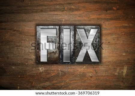 """The word """"Fix"""" written in vintage metal letterpress type on an aged wooden background. - stock photo"""