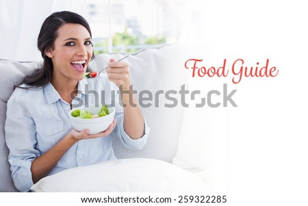 The word food guide against cheerful woman relaxing on the sofa eating salad - stock photo