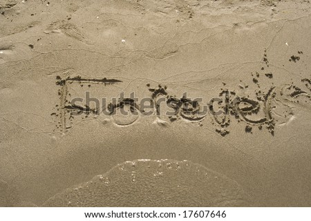 The word forever is written in sand and partially washed away. - stock photo