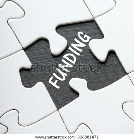 The word Funding in white text on a blackboard as revealed by a missing jigsaw puzzle piece - stock photo