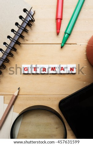 "The word ""German"" spelled using letter tiles on wooden background  - stock photo"