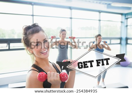 The word get fit and smiling woman lifting weights while women doing aerobics against badge - stock photo