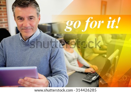 The word go for it! against teacher holding a tablet pc - stock photo