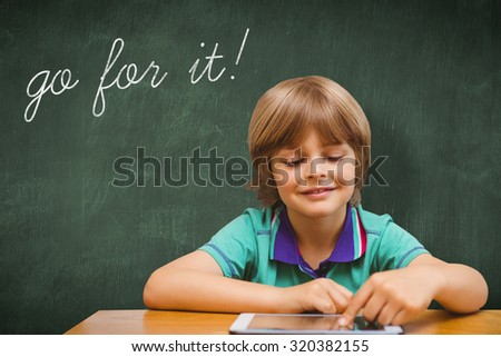The word go for it! and pupil using tablet pc against green chalkboard