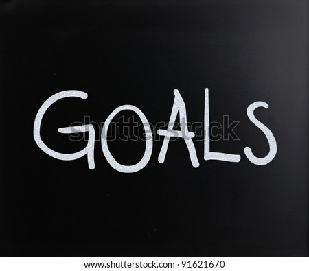 "The word ""Goals"" handwritten with white chalk on a blackboard"