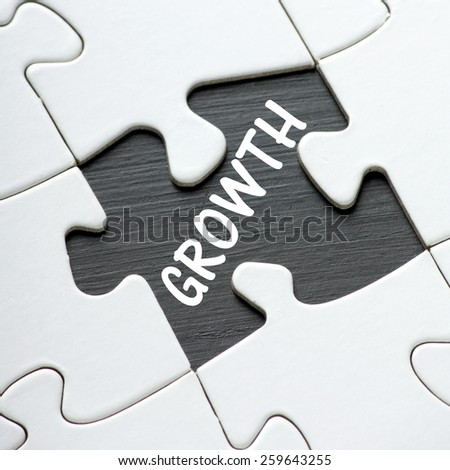 The word Growth on a blackboard revealed by a missing jigsaw puzzle piece - stock photo