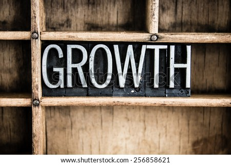 "The word ""GROWTH"" written in vintage metal letterpress type in a wooden drawer with dividers. - stock photo"