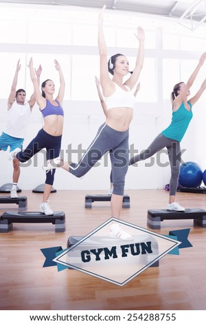 The word gym fun and fitness class performing step aerobics exercise against badge - stock photo
