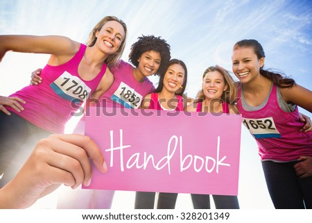 The word handbook and hand holding card against five smiling runners supporting breast cancer marathon