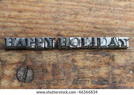the word happy holiday in letterpress type on a wooden background. - stock photo