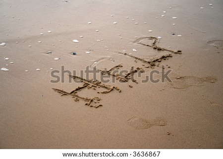 The word Help written in sand next to the shore - stock photo