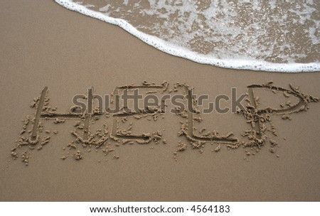 The word Help written in sand next to the shore with a wave washing over - stock photo