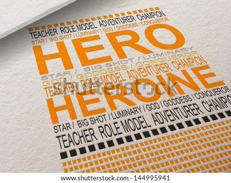 The word Hero letterpressed into paper with associated words around it. - stock photo