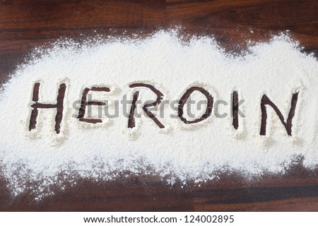 The word heroin written in a white powder - stock photo