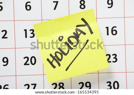 The word Holiday written on yellow sticky note paper stuck to a wall calendar background - stock photo
