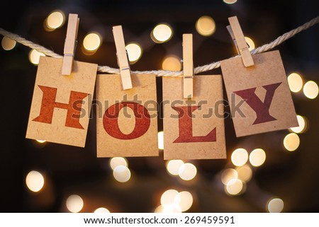 The word HOLY spelled out on clothespin clipped cards in front of glowing lights. - stock photo