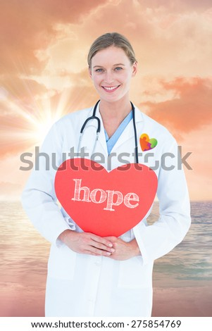The word hope and doctor holding red heart card against sunrise over magical sea - stock photo