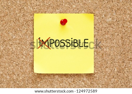 The word Impossible turning into Possible on yellow sticky note. - stock photo