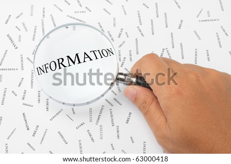 The word, INFORMATION is magnified. - stock photo
